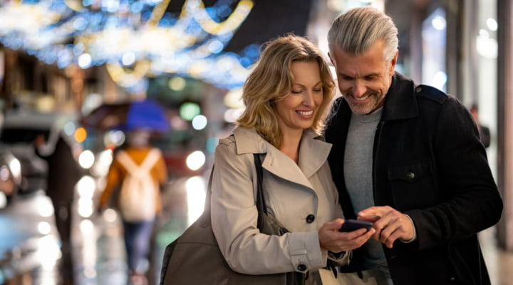 Happy couple on city street looking at smartphone